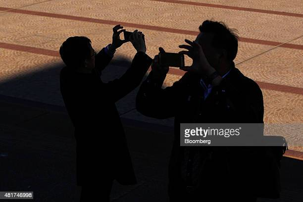 Tourists take photographs with their mobile phones near the Sydney Opera House in Sydney Australia on Tuesday July 21 2015 Tired hotels outdated...