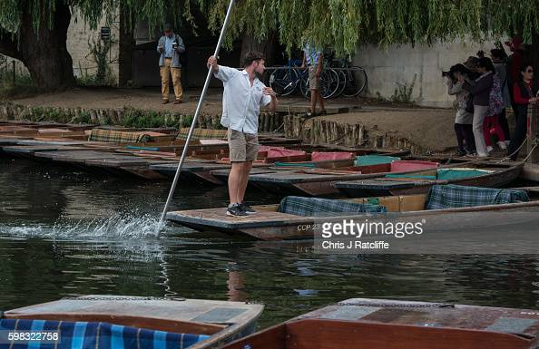 Tourists take photos as they wait for a ride in a punt on the River Cam on September 1 2016 in Cambridge England Punting is popular with many...