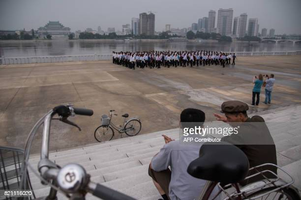Tourists take photos before the Taedong river in Pyongyang on July 23 2017 The Westerners lined up before giant statues of North Koreas founder Kim...