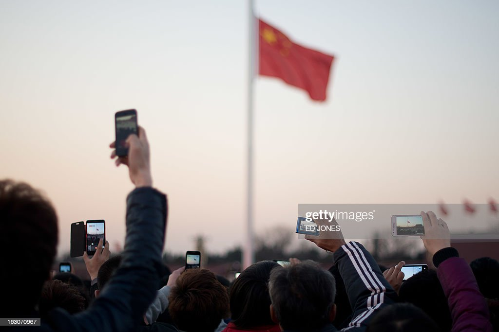 Tourists take photos during the daily flag-lowering ceremony on Tiananmen Square in Beijing on March 4, 2013. Thousands of delegates from across China meet this week to seal a power transfer to new leaders whose first months running the Communist Party have pumped up expectations with a deluge of propaganda. AFP PHOTO / Ed Jones