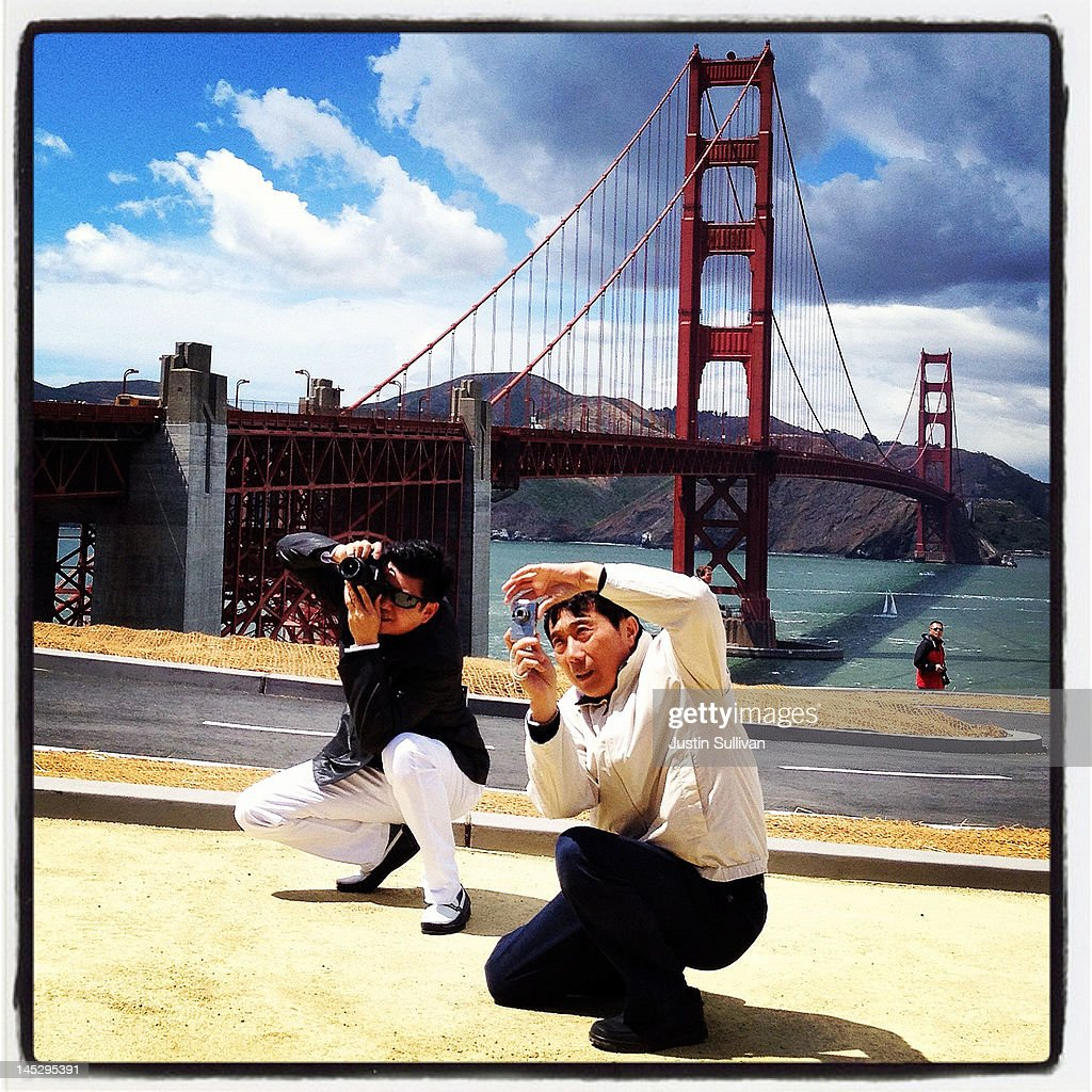 Tourists take photos in front of the Golden Gate Bridge on May 25, 2012 in San Francisco, California. The Golden Gate Bridge, Highway and Transportation District is preparing for the 75th anniversary of the iconic Golden Gate Bridge that will be marked with a festival on May 26 - 27 that will feature music, displays of bridge artifacts and art exhibits. The 1.7 mile steel suspension bridge, one of the modern Wonders of the World, opened to traffic on May 27, 1937.