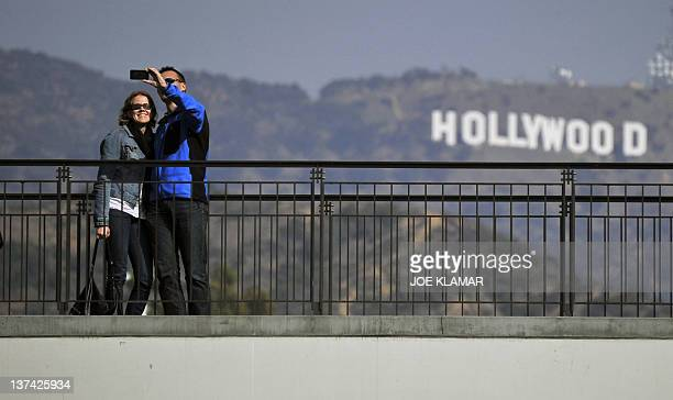 Tourists take photos in front of the iconic Hollywood sign on January 20 2012 in Los Angeles California where police found on January 18 2012 a human...