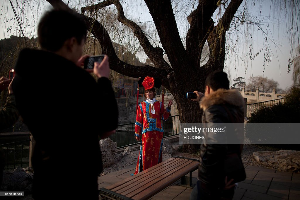 Tourists take photos of a woman dressed in Qing dynasty style clothing in Beihai park in Beijing on December 4, 2012. The latest batch of purchasing managers' indexes from HSBC show manufacturing activity in China hit a 13-month high, while India also saw its strongest expansion since June. AFP PHOTO / Ed Jones