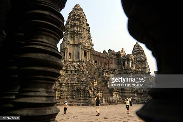 Tourists take photos of the Angkor Wat temple in Siem Reap province on March 20 2015 US First Lady Michelle Obama flew into Cambodia at the tourist...