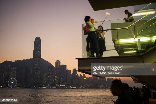 Tourists take photos of the Hong Kong skyline from a viewing deck in Kowloon along Victoria Harbour on December 1 2016 / AFP / Anthony WALLACE