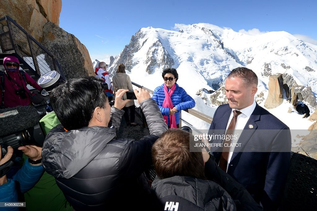 Tourists take photos of the Vice Premier of China, Liu Yandong (Rear) with the Mont-Blanc peak in background, during Liu Yandong's visit on June 29, 2016 at the top of the Aiguille du Midi mountain above Chamonix, French Alps. / AFP / JEAN
