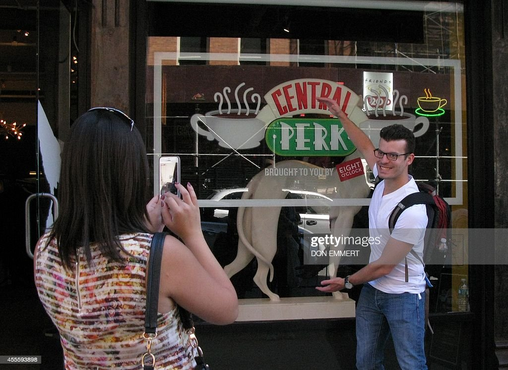 Tourists take photos outside a temporary 'pop up' reproduction of the 'Central Perk' coffee shop a center piece set of the television situation...