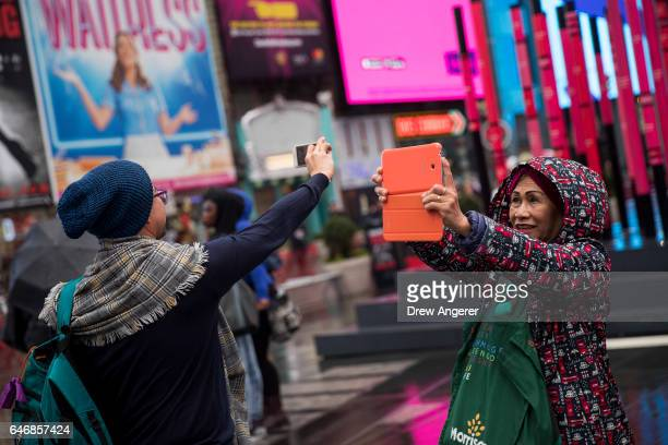 Tourists take photos with their smart phones in Times Square March 1 2017 in New York City NYC Company the city's tourism marking agency released a...