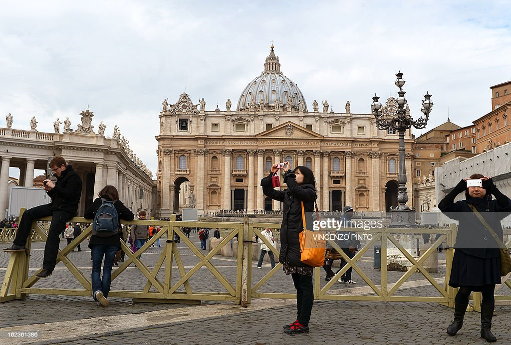 Tourists take picture at St Peter's square on February 22, 2013 as Pope Benedict XVI began a week-long spiritual retreat out of the public eye ahead of his resignation on February 28 with the field of candidates to succeed him still wide open. sAFP PHOTO / VINCENZO PINTO