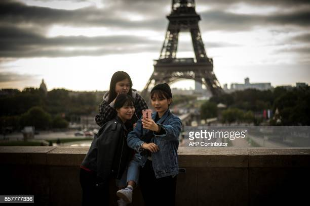 Tourists take pictures at sunrise at the eiffel tower on October 5 2017 in Paris / AFP PHOTO / Lionel BONAVENTURE
