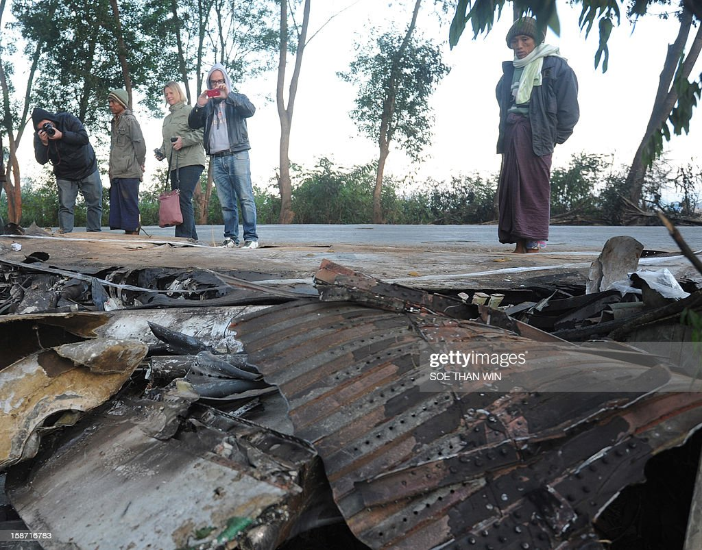 Tourists take pictures at the scene of a plane crash near Heho airport in southern Shan state on December 26, 2012. Myanmar was investigating the cause of an air accident that left two people dead and 11 injured when a passenger jet packed with foreign tourists crash-landed and caught fire. AFP PHOTO/Soe Than WIN