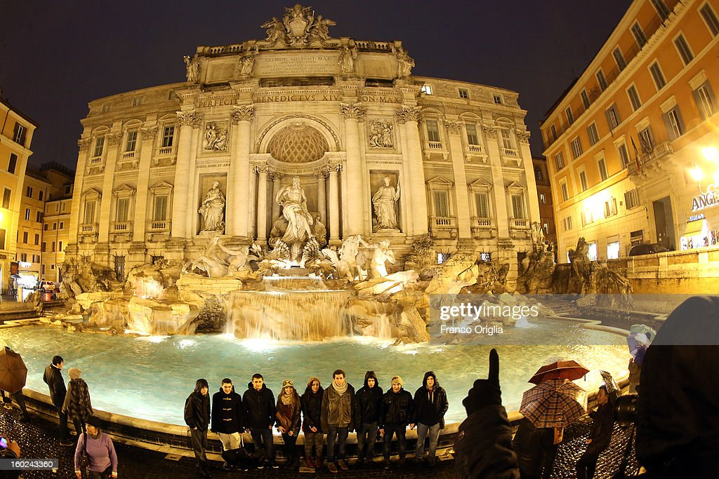 Tourists take pictures at Trevi Fountain on January 28, 2013 in Rome, Italy. FENDI Chairman and CEO Pietro Beccari together with Karl Lagerfeld and Silvia Venturini Fendi and the representatives of the City of Rome, including the Mayor Gianni Alemanno, today announced the sponsorship of the restoration of Rome's most iconic fountain.