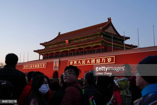 Tourists take pictures during the daily flag decline ceremony at at Tian'anmen Square on March 1 2017 in Beijing China Armed police are being...