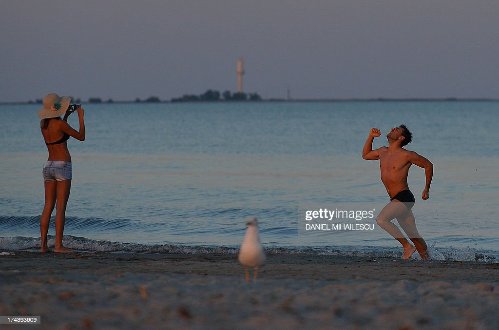 Tourists take pictures during the sunset on the Black Sea beach of Sulina on July 24, 2013. Sulina, the most eastern city of European Union is a town and a free port in Dobrogea historical region of Romania, at the end of the Danube Delta. According to the official statistics it has a population with around 5000 inhabitants and it can be only reached by the water from the Danube or Black Sea. AFP PHOTO / DANIEL MIHAILESCU
