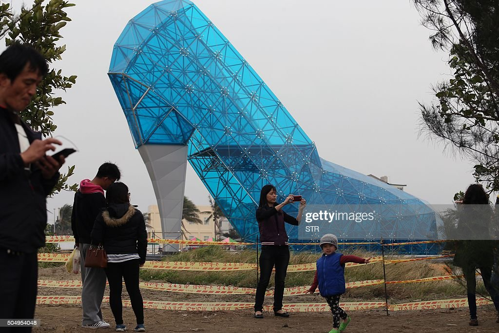 TOPSHOT Tourists take pictures in front of a shoeshaped church in southern Chiayi on January 11 2016 The church which measures 55 feet tall and 36...
