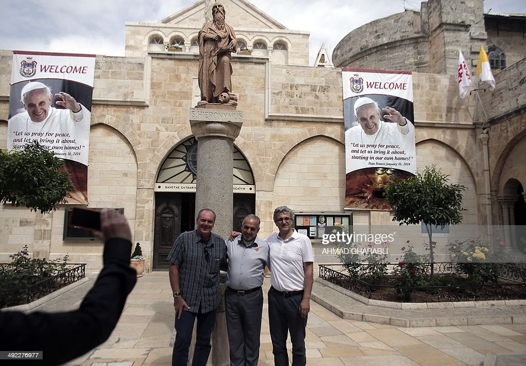 Tourists take pictures in front of banners bearing the portrait of Pope Francis displayed on the wall of the Saint Catherine's Church in the Church of Nativity, in the West Bank city of Bethlehem, on May 19, 2014 ahead of his visit to the Holy Land. The upcoming pilgrimage to the Holy Land by Pope Francis is set to start in Jordan on May 24. Early the following day, he leaves for the West Bank town of Bethlehem, then flies to Israel where he will stay until the evening of May 26. AFP PHOTO / AHMAD GHARABLI