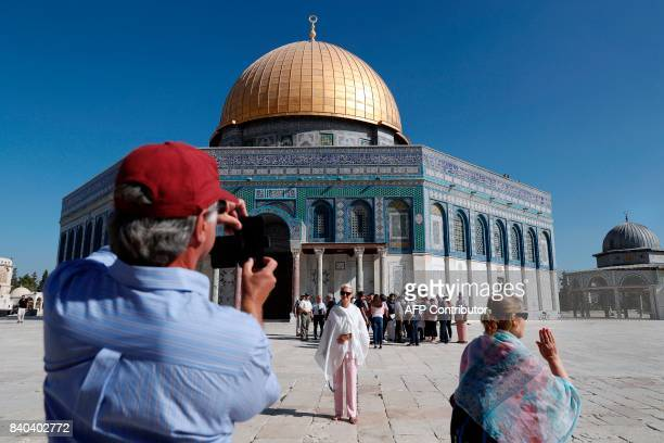 Tourists take pictures in front of the Dome of the Rock inside the the flashpoint AlAqsa mosque compound also known as the Temple Mount complex in...
