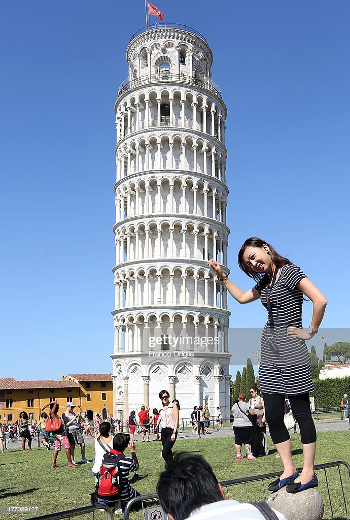 Tourists take pictures in front of the Leaning Tower of Pisa, Torre pendente di Pisa, on August 10, 2013 in Pisa, Italy.