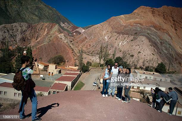 Tourists take pictures in Purmamarca town at the Quebrada de Purmamarca in the Argentine northern province of Jujuy taken on July 11 2011 The colors...