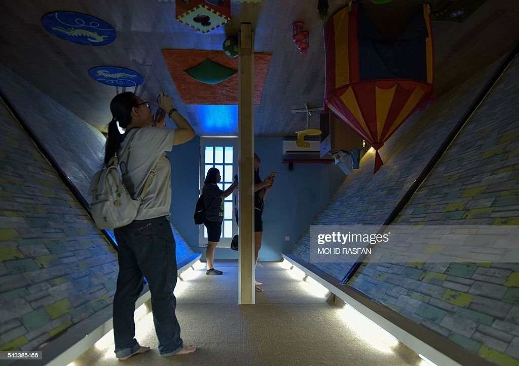 Tourists take pictures inside the Kuala Lumpur Upside Down House at KL Tower in Kuala Lumpur on June 28, 2016. Kuala Lumpur Upside Down House is a two-storey house and is the latest attraction for tourists arriving to the Malaysian capital where everything inside such as the furniture are placed in an upside down position. / AFP / MOHD