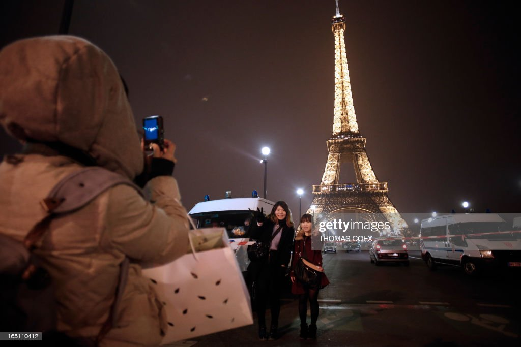 Tourists take pictures near a cordoned off Eiffel Tower in Paris on March 30, 2013. The Eiffel Tower was evacuated in the evening on March 30 after an anonymous phone call announced an attack, according to a police source. According to the police source, the perimeter of the monument was secured and about 1,400 people were evacuated shortly before 21h00. AFP PHOTO / THOMAS COEX
