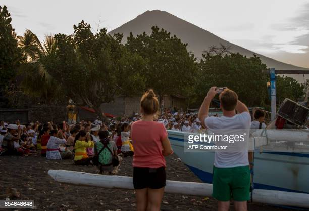 Tourists take pictures of a prayer as Mount Agung volcano is seen in the background at Amed beach in Karangasem on the island of Bali on September 27...
