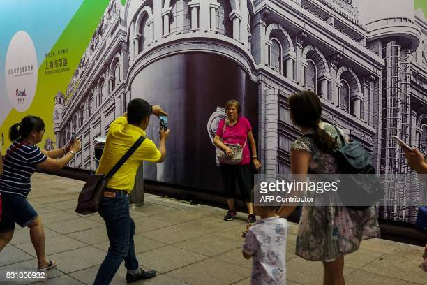 Tourists take pictures of a relative against a photo backdrop in Shanghai on August 14 2017 / AFP PHOTO / CHANDAN KHANNA