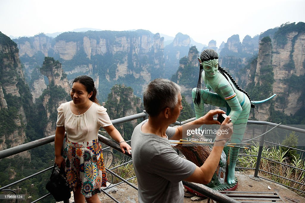 Tourists take pictures of an Avatar sculpture at the Tianzi Mountain on September 1, 2013 in Zhangjiajie, China. Zhangjiajie National Forest park is a popular tourist destination in the Hunan province, home to striking sandstone and quartz cliffs and famously known for renaming a peak after the mountain formations inspired the fictional world of 'Pandora' in James Cameron's film, 'Avatar'.