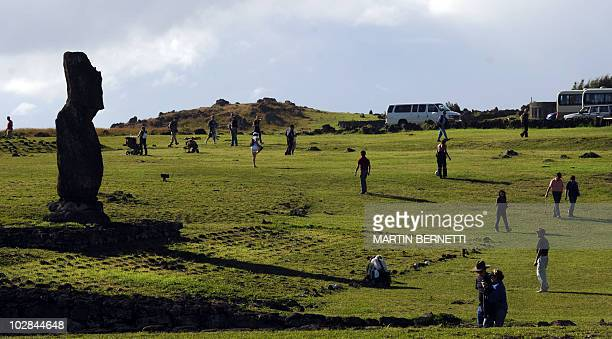 Tourists take pictures of Moais stone statue of the Rapa Nui culture on Easter Island 3700 km off the Chilean coast in the Pacific Ocean on July 9...