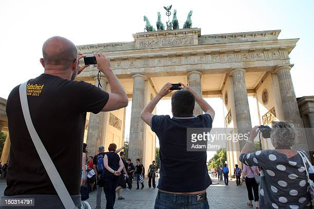 Tourists take pictures of the Brandenburg Gate on August 15 2012 in Berlin Germany In 2010 nine million tourists visited the German capital and ten...