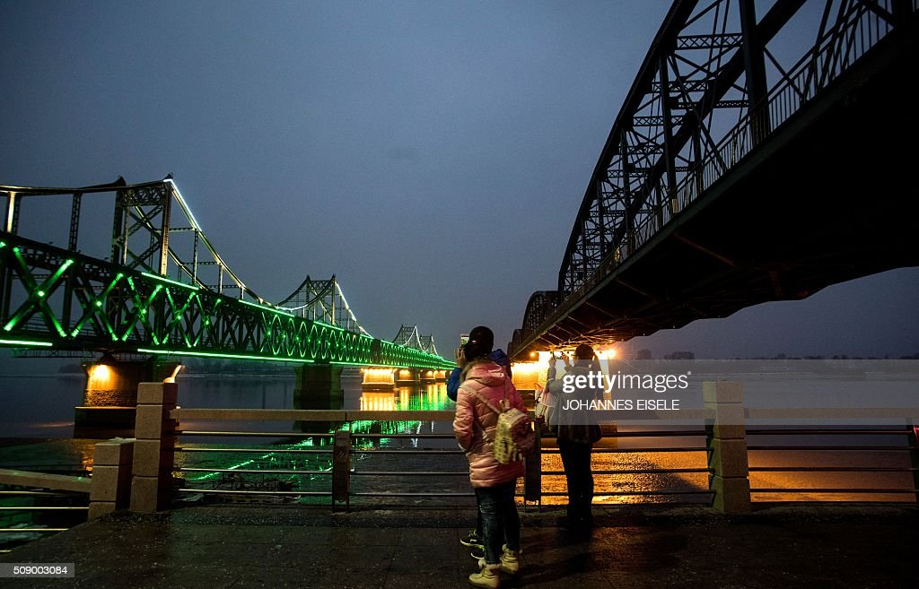 Tourists take pictures of the bridge on the banks of the Yalu River at the Chinese border town of Dandong across from the North Korean town of Sinuiju on February 8, 2016. The UN Security Council strongly condemned North Korea's rocket launch on February 7 and agreed to move quickly to impose new sanctions that will punish Pyongyang for 'these dangerous and serious violations.' AFP PHOTO / JOHANNES EISELE / AFP / JOHANNES EISELE