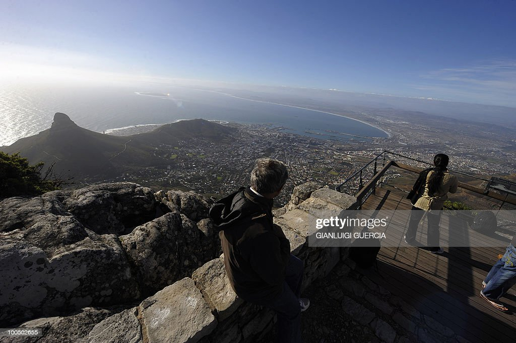 Tourists take pictures of the city of Cape Town as seen from the top of Table Mountain at the arrival station of the Table mountain cableway on May 7, 2010 in Cape Town, South Africa. Table Mountain cableway has been running for over 80 years and the cars feature a floor which can rotate while ascending to give passengers a 360 degree panoramic views.