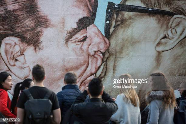 Tourists take pictures of the graffiti 'My God Help Me To Survive This Deadly Love' by artist Dimitry Vrubel depicting Leonid Brezhnev leader of the...