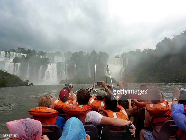 Tourists take pictures of the Iguacu Falls on an adventure boat on April 28 2010 The waterfall system consists of 275 falls along 27 kilometers of...