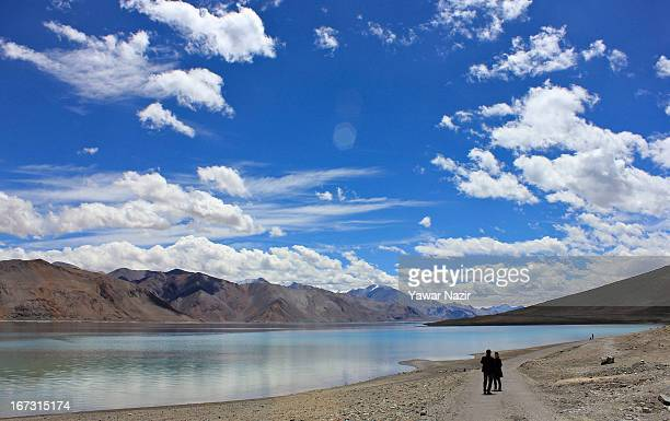 Tourists take pictures of the lake in Pangong a disputed territory between India and China on August 4 2012 in Ladakh Indianadministered Kashmir