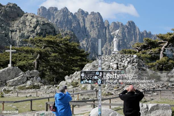 Tourists take pictures of the NotreDame des Neiges statue at the Bavella pass close to the GR20 trek in the Bavella Mountains in Zonza on the French...
