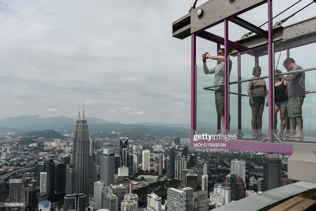Tourists take pictures of the panoramic view of the city from the Sky Box at KL Tower, the world's seventh tallest telecommunications tower, in Kuala Lumpur on May 24, 2016. Officially opened on May 20, the Sky Box has been the latest attraction for tourists arriving to the Malaysian capital. It stands 300 metres above ground and can fit six people at any one time, and offers spectacular views of the Kuala Lumpur skyline, including the iconic Petronas Twin Towers. / AFP / MOHD