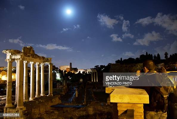 Tourists take pictures of the Roman Forum with the moon rising in the sky of Rome on November 4 2014 AFP PHOTO / VINCENZO PINTO