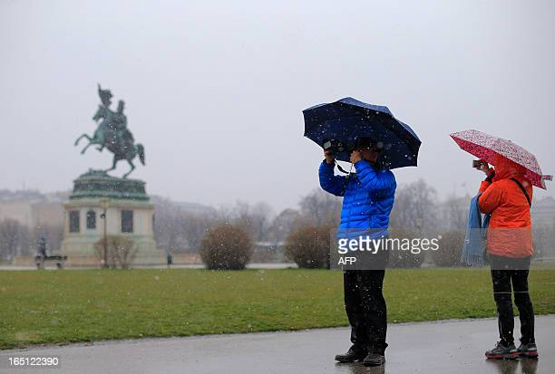 Tourists take pictures on a cold Easter sunday with light snowfall in Vienna on March 31 2013 AFP PHOTO / ALEXANDER KLEIN