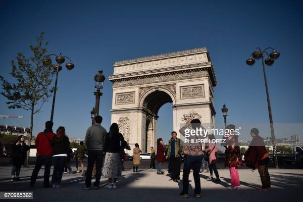 Tourists take pictures on the Champs Elysees avenue near the Arc de Triomphe monument in Paris on April 21 a day after a gunman opened fire on police...