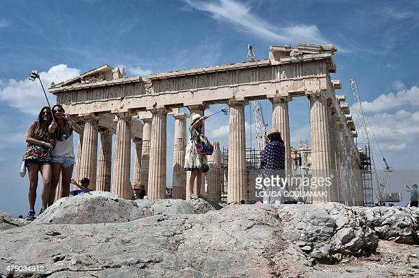 Tourists take pictures with a selfie stick as they visit the Acropolis in Athens on June 30 2015 Greece appeared set Tuesday to default on a key IMF...