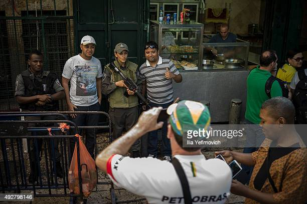 Tourists take pictures with security guards in the old city on October 15 2015 in Jerusalem Israel After a wave of Palenstinian attacks Prime...