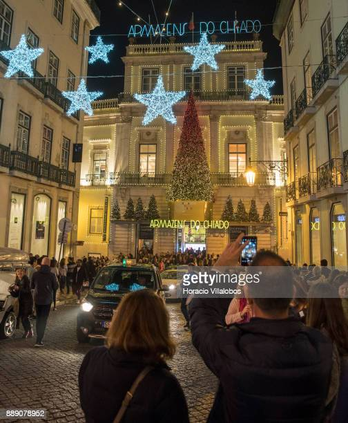 Tourists take pictures with their cellphones of Armazens do Chiado Shopping Center Christmas and New Year light displays at the end of Rua Garrett on...