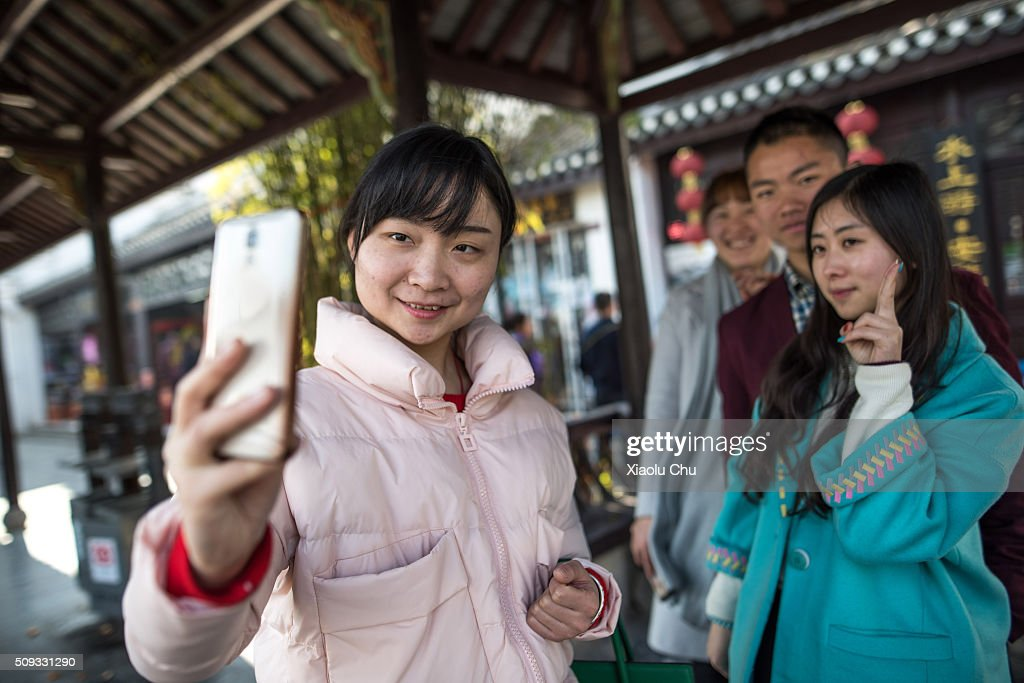 Tourists take 'selfies' during Chinese Spring Festival on February 10, 2016 in Hefei, China. The Spring Festival will be celebrated February 7-16 and is the most important holiday in China.