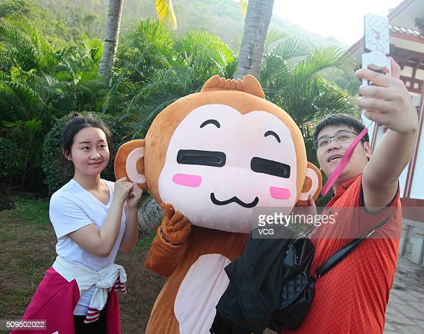 Tourists take selfies with a cartoon monkey doll during the Spring Festival holiday on February 10 2016 in Sanya Hainan Province of China The...