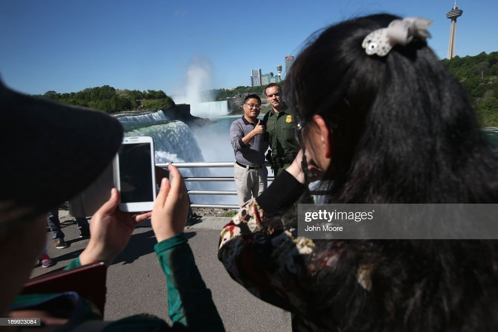 Tourists take snapshots with a U.S. Border Patrol agent near Niagara Falls on June 4, 2013 in Niagara Falls, New York. The falls, which lie directly on the U.S.-Canada border, are a major destination for American and international tourists alike. Border Patrol agents detain foreign travelers who have overstayed their visas as well as undocumented immigrants who attempt to illegally cross the international bridge in Niagara Falls.