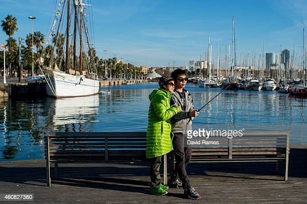 Tourists takes a photo with a selfie stick prior to the 105th Barcelona Traditional Christmas Swimming Cup at the Old Harbour of Barcelona on...
