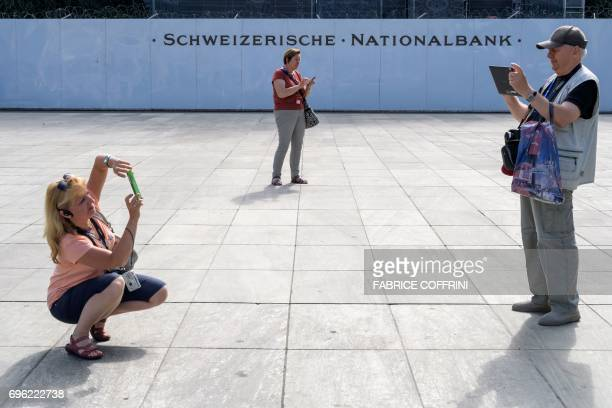 Tourists takes a picture next to a sign of the Swiss National Bank in front of the building under renovation on June 15 2017 in Bern The Swiss...