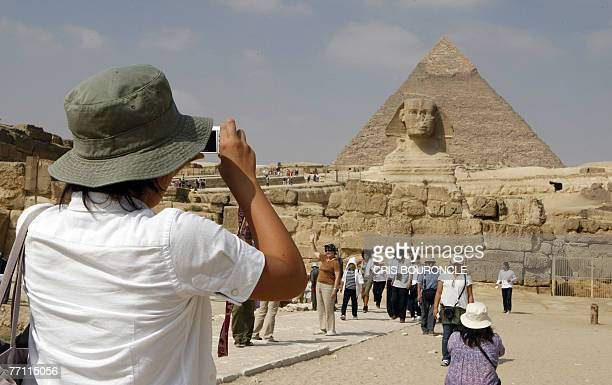 A tourists takes a picture of the famous Great Sphinx with Khafre's Pyramid in the background at the Giza Plateau on the outskirts of Cairo 30...