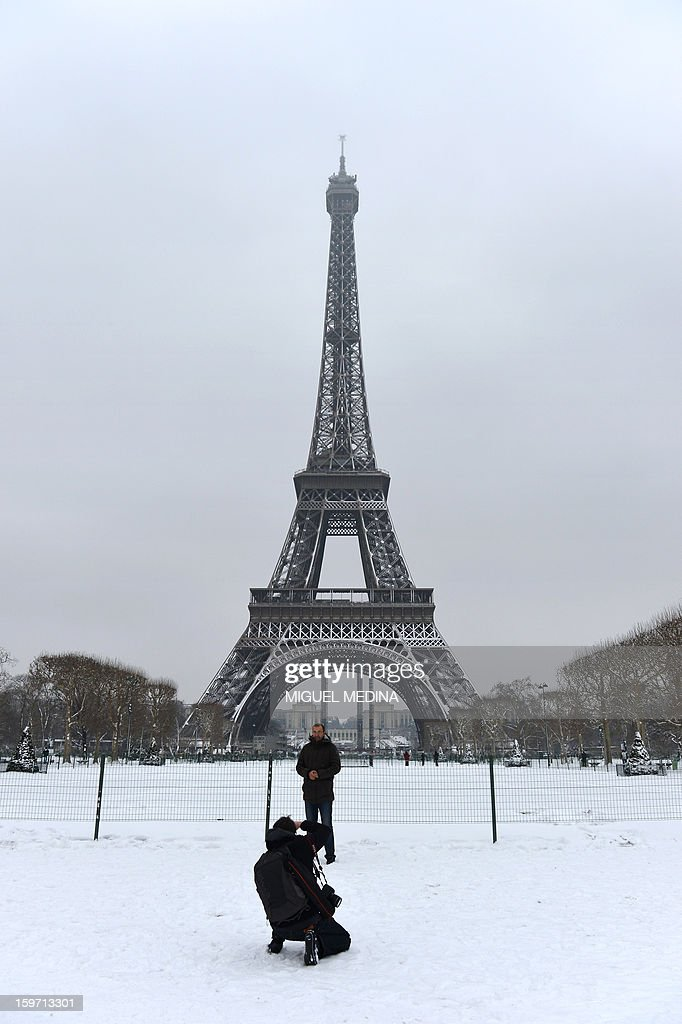Tourists takes pictures near the Eiffel tower on January 19, 2013 in Paris, after the snow fell over the French capital overnight.
